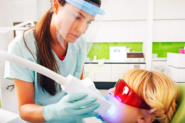 dentist whitening a woman's teeth