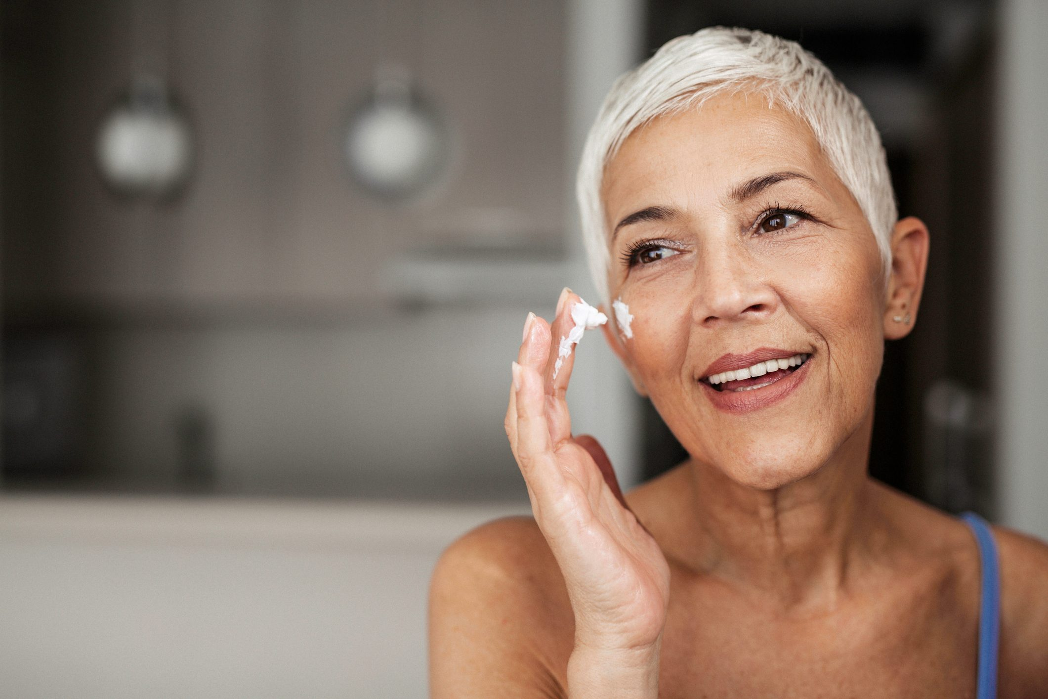 senior woman applying sunscreen to her face