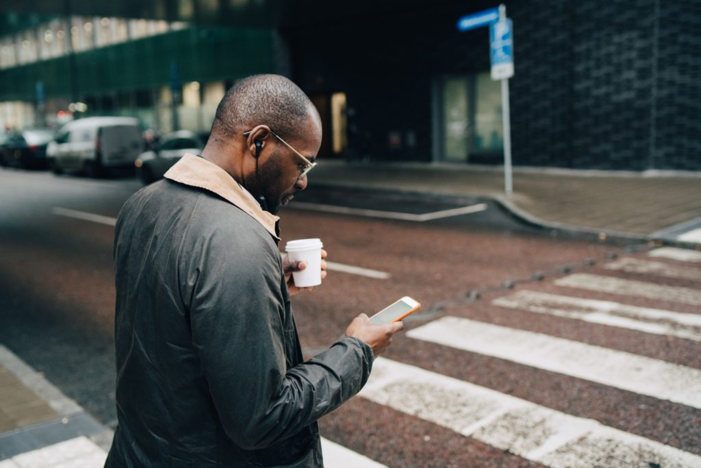 businessman walking on street looking at phone