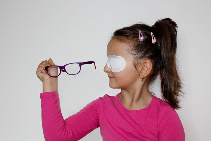 young girl with eye patch holding eyeglasses
