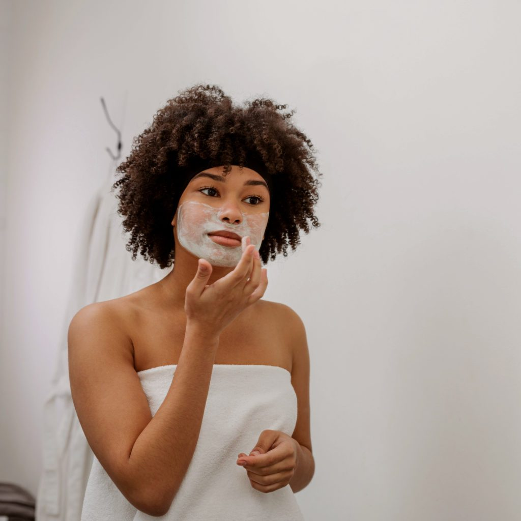 woman applying face mask on face in bathroom