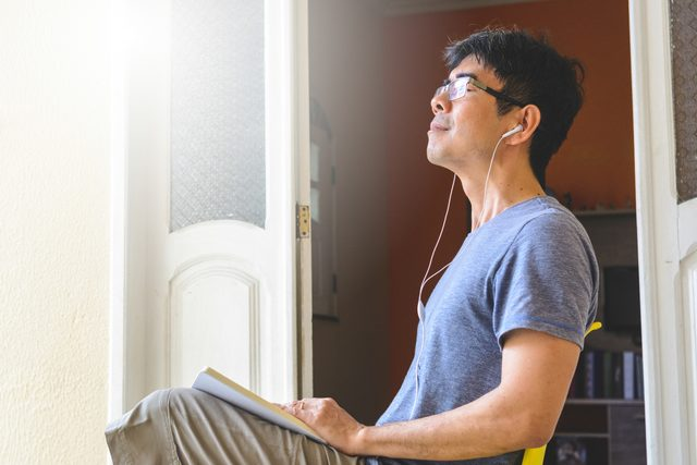 man taking a deep breath and relaxing at home