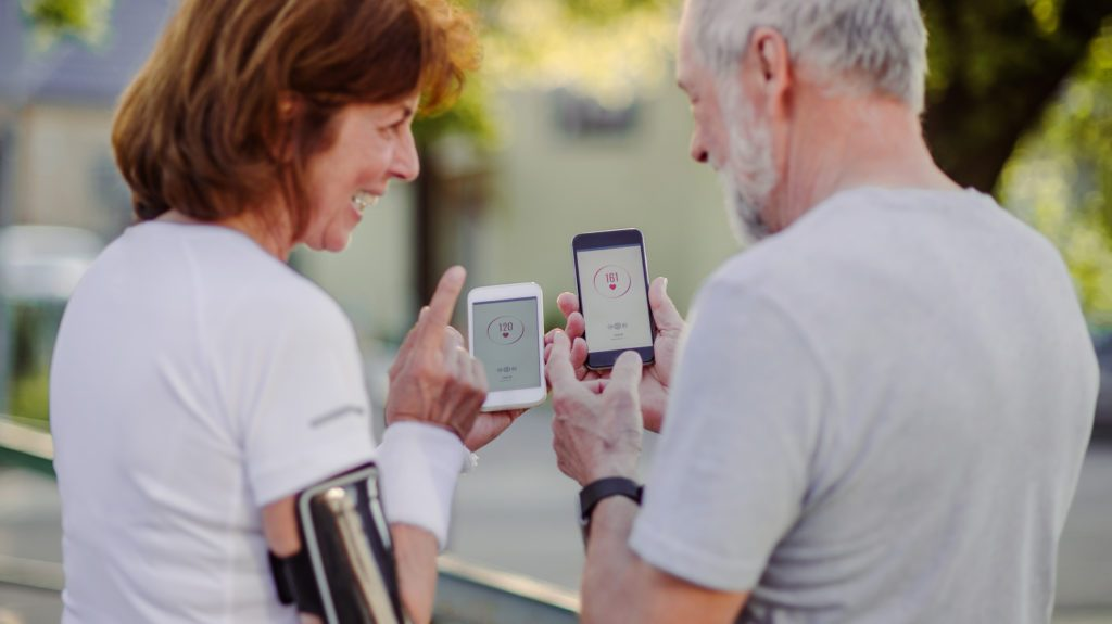 older couple using fitness app while exercising