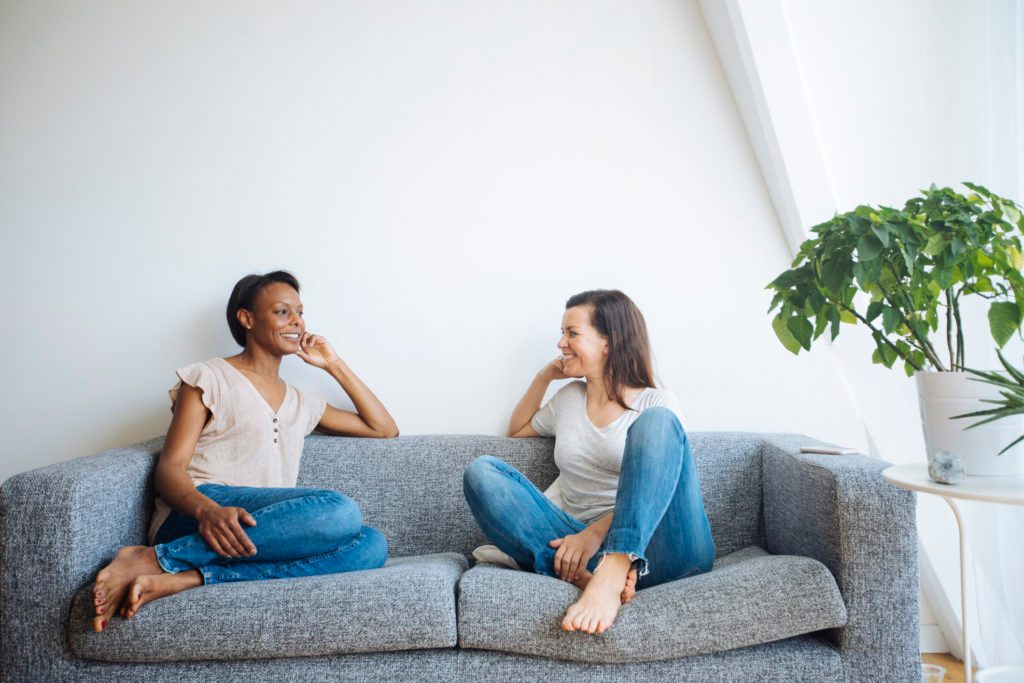 two friends sitting on couch at home talking