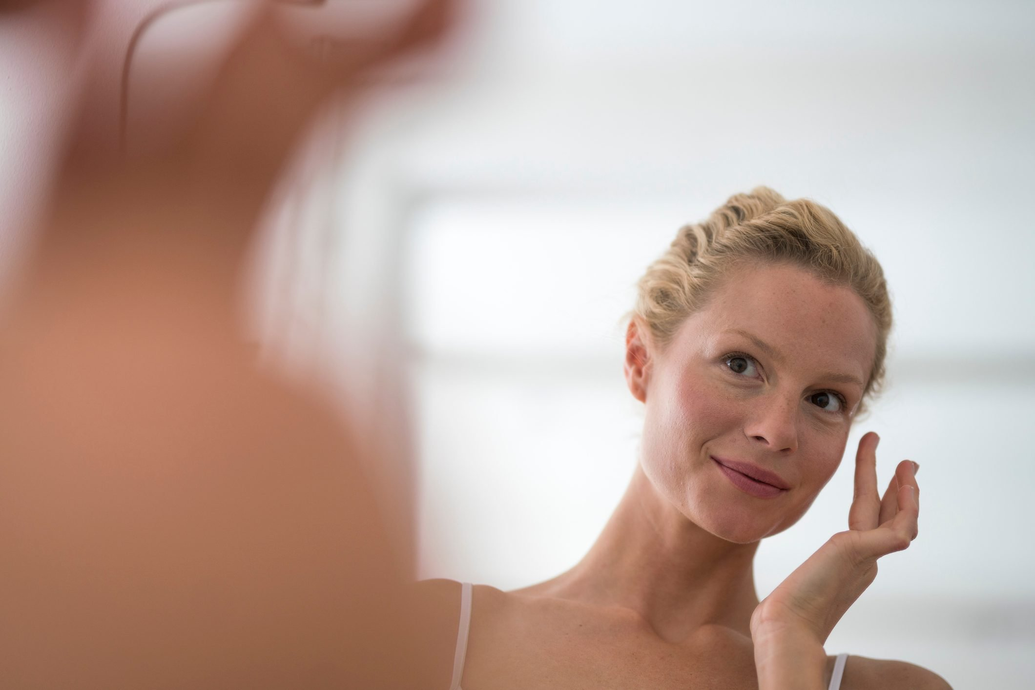 woman looking in mirror applying skin care on face
