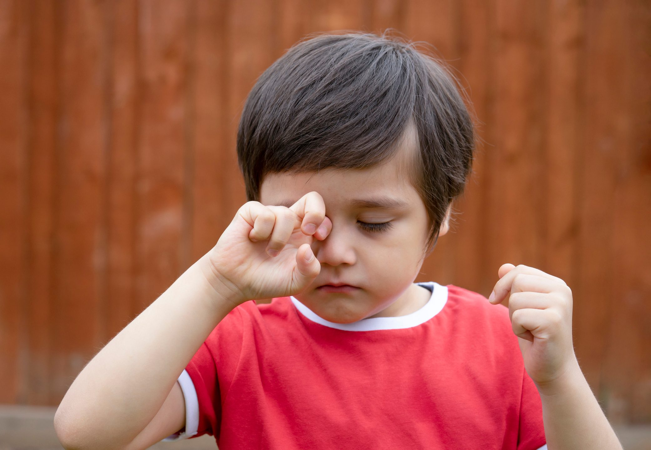 young boy rubbing his eye