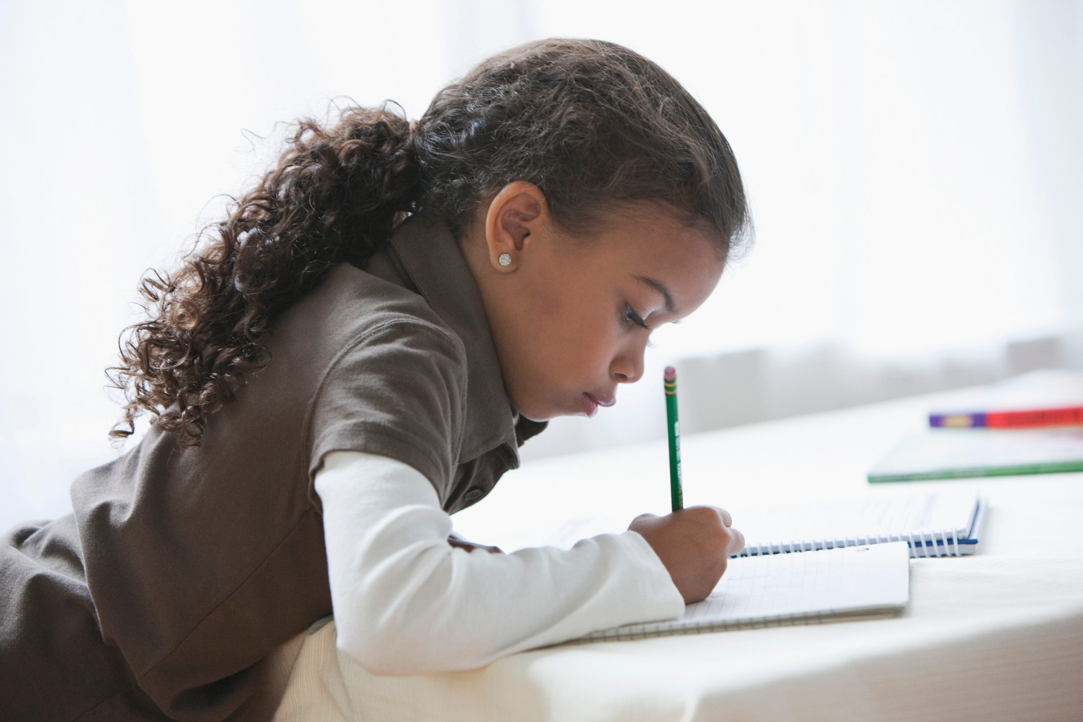 young girl writing doing homework