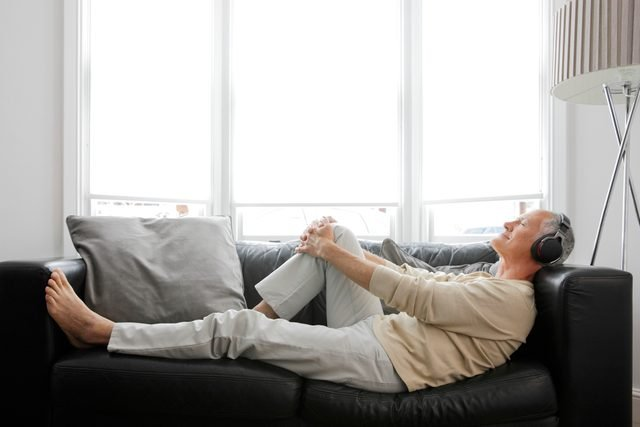 man laying on couch listening to music or podcast in headphones