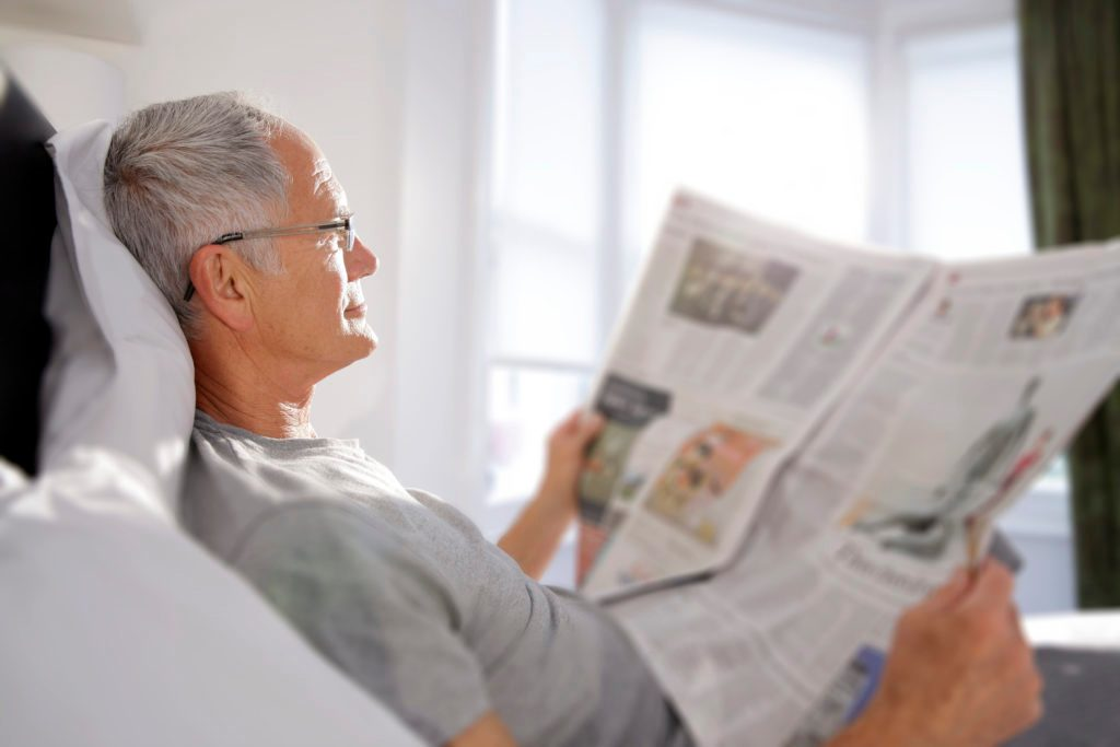 man reading newspaper in bed