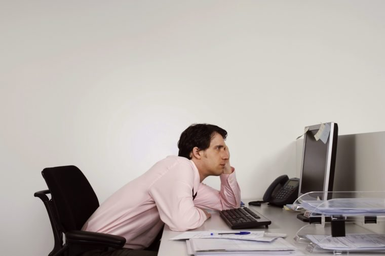 man slouching at work desk