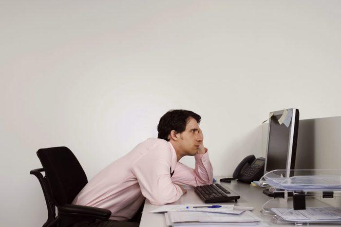 man slouching at work desk