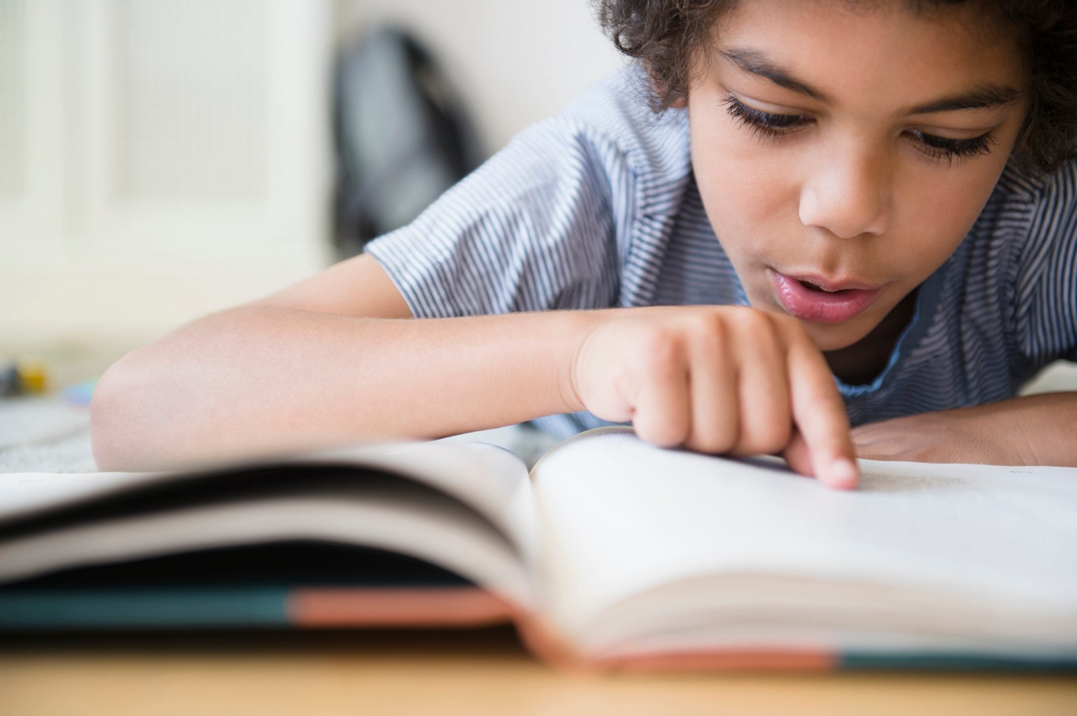 young boy reading a book close up