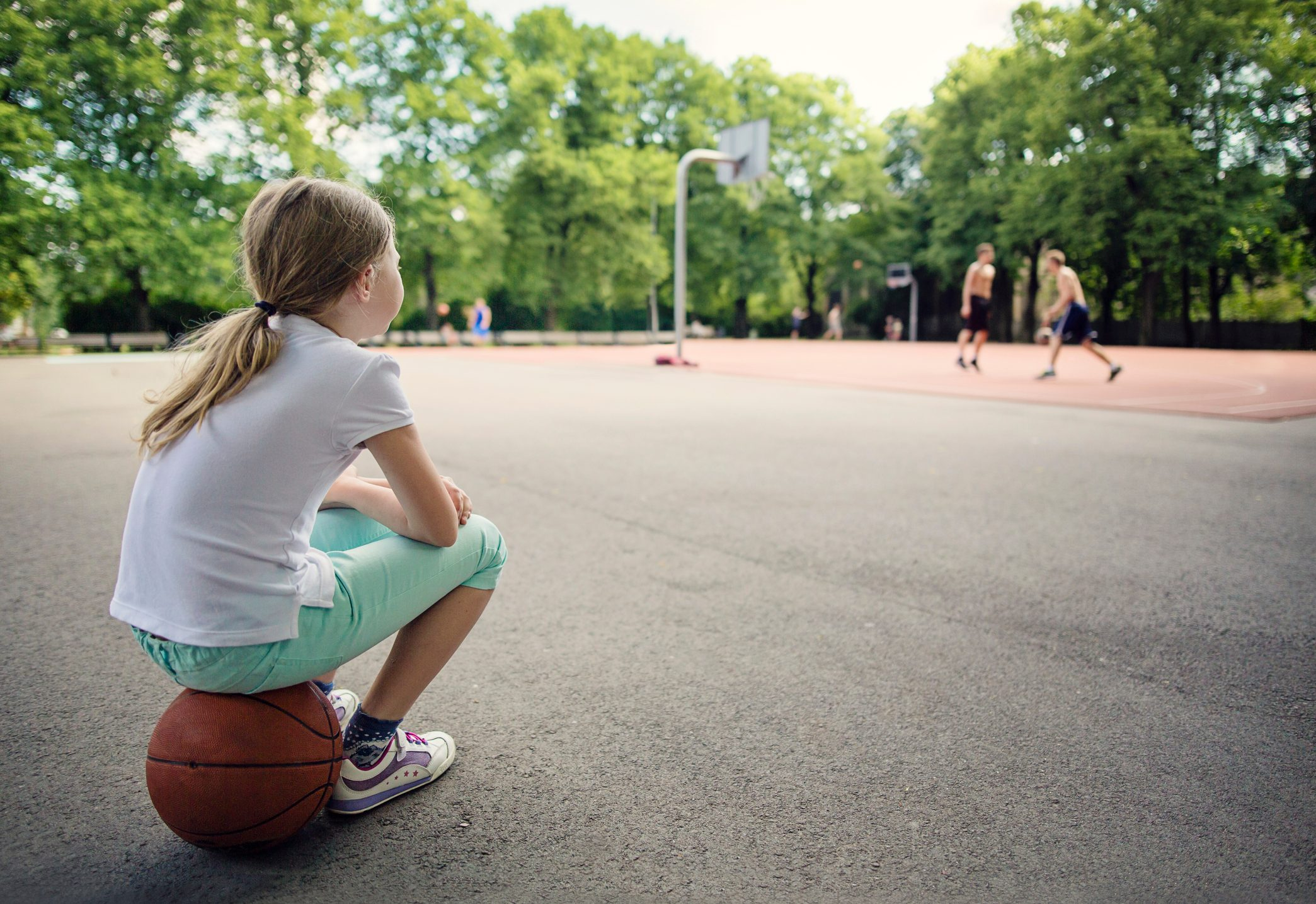 young girl sitting on basketball watching people play
