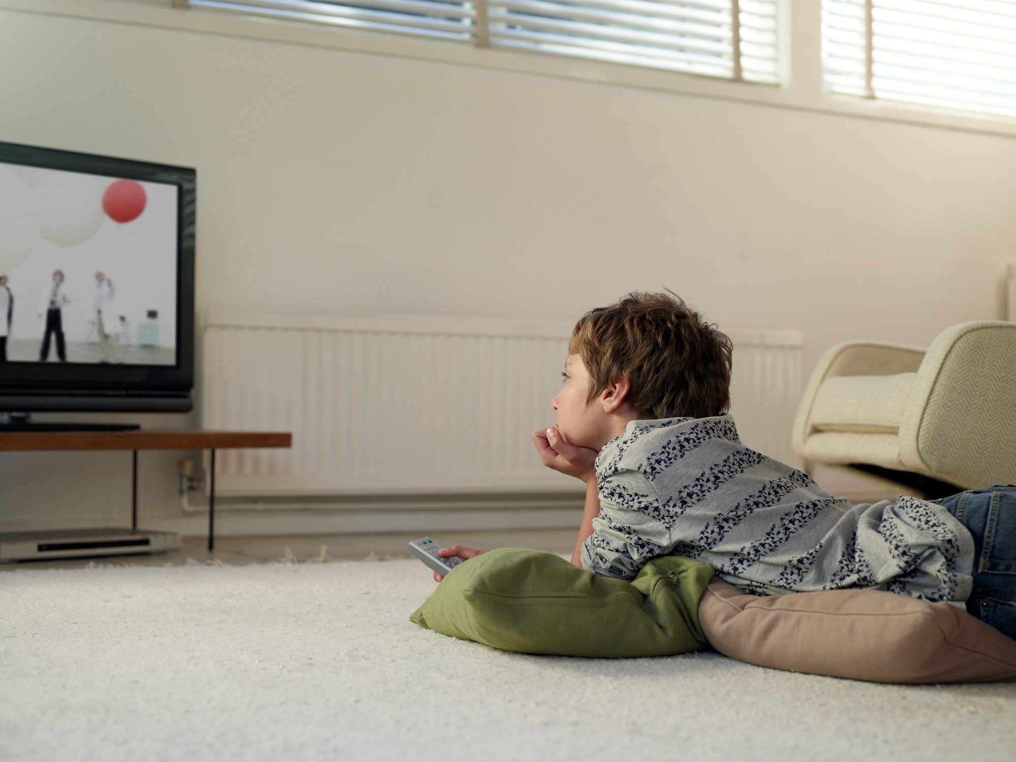 boy lying on floor watching television