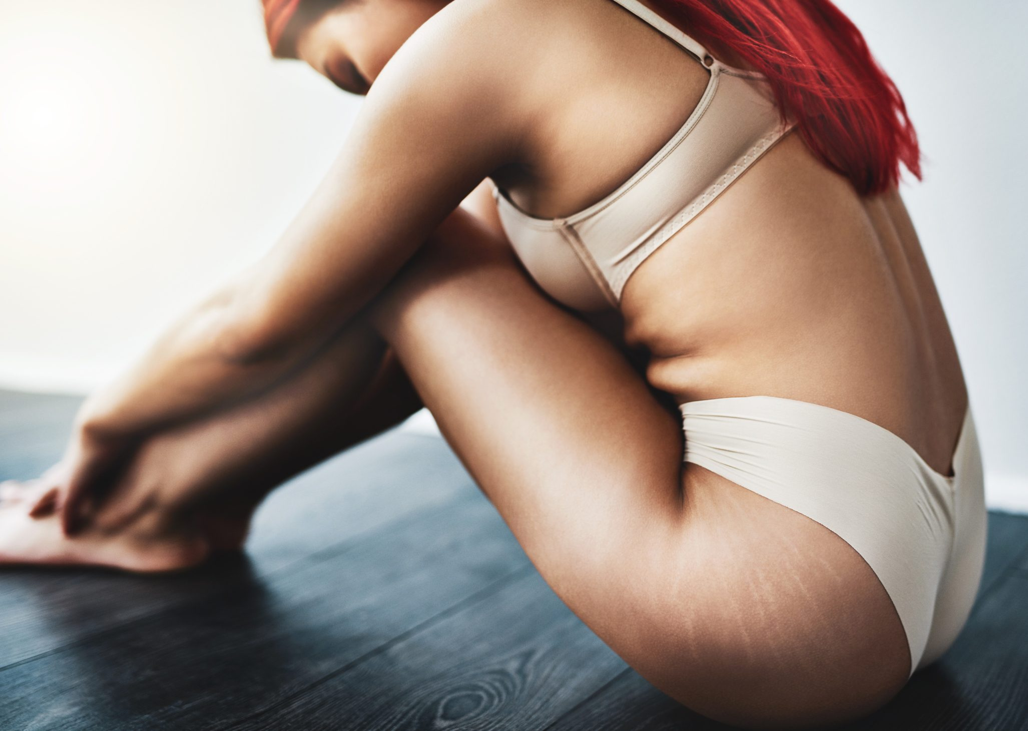 cropped shot of woman sitting down with stretch marks