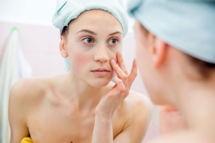 woman just out of the shower checking her face in the mirror