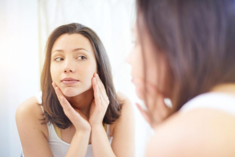 Woman in a white tank top looking at her skin in the mirror.