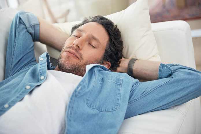 Man with hands behind his head asleep on a couch