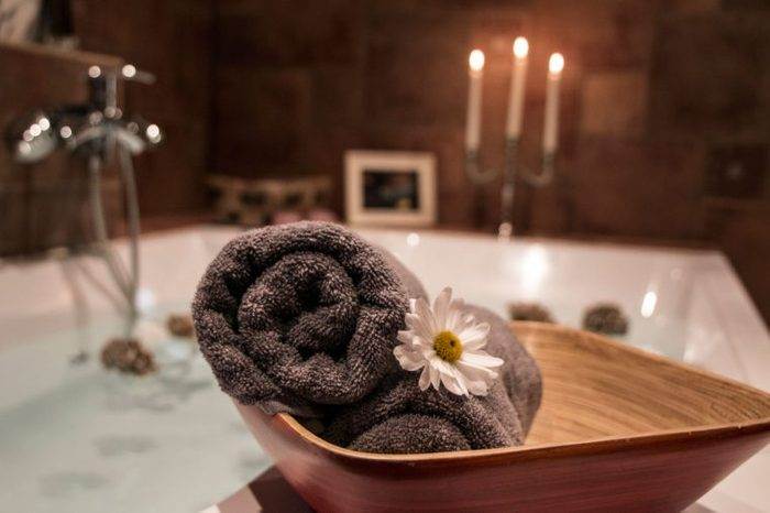 rolled towels next to candlelit bathtub