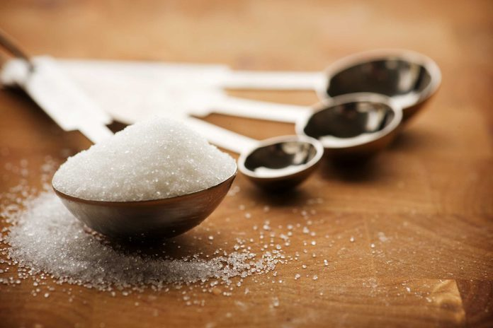 measuring spoons, one filled with sugar