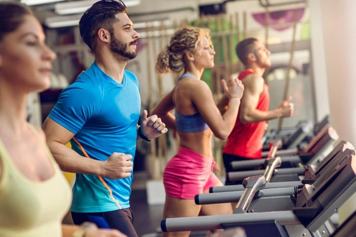 people running on treadmills in a gym