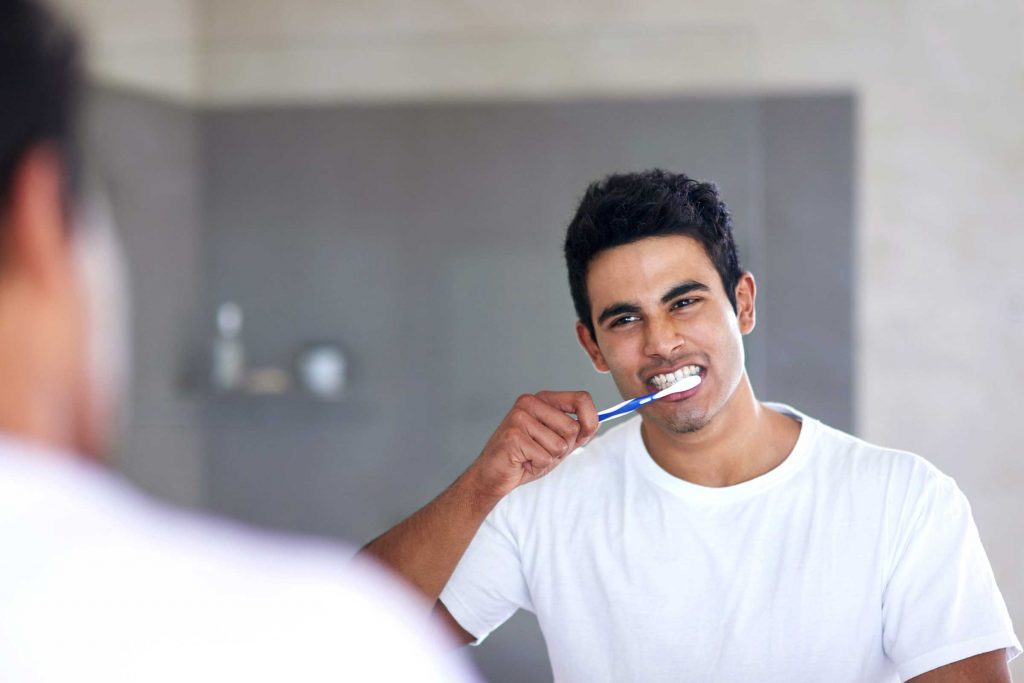 man brushing his teeth in front of a mirror