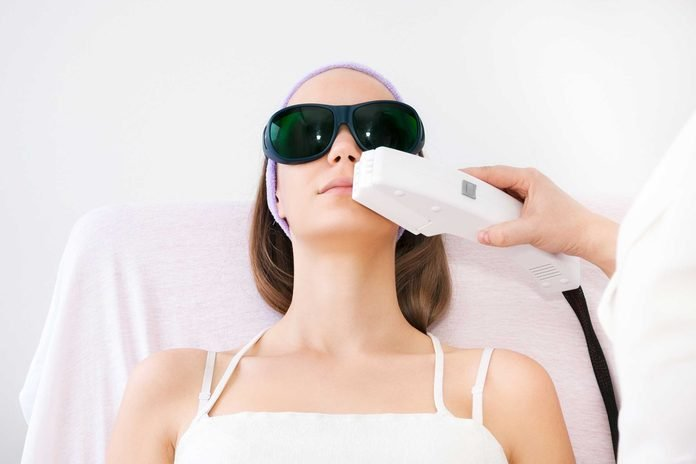 Woman in sunglasses getting laser/light treatment