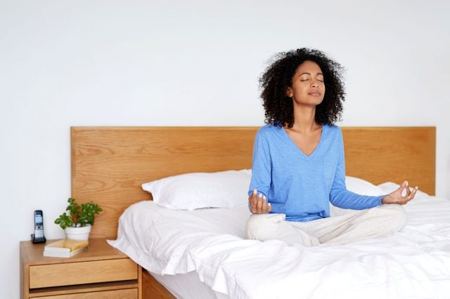 woman meditating in bed