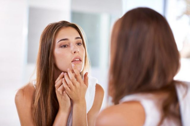 Woman looking in the mirror at a spot on her chin.