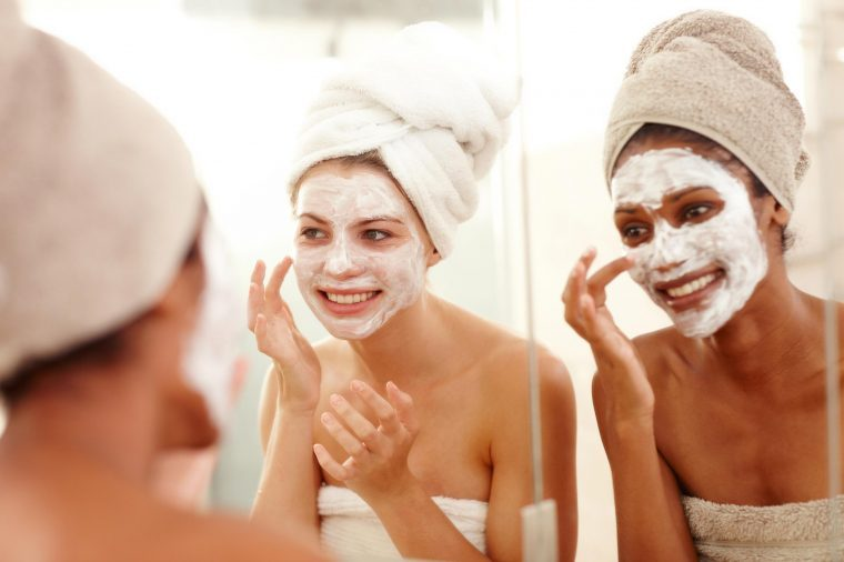 Two women wearing white skin masks looking in the mirror.