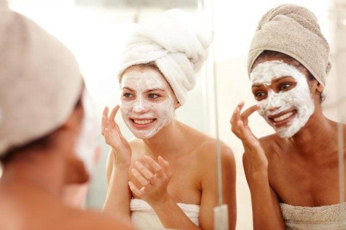 Two women wearing white skin masks looking in the mirror.