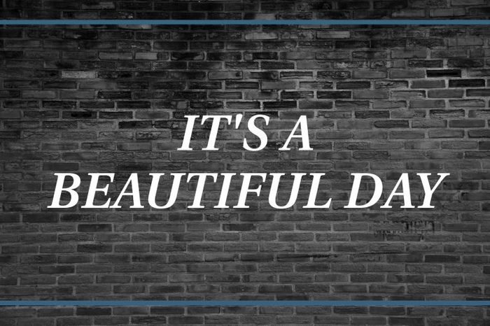 Brick wall background that says: It's a beautiful day.