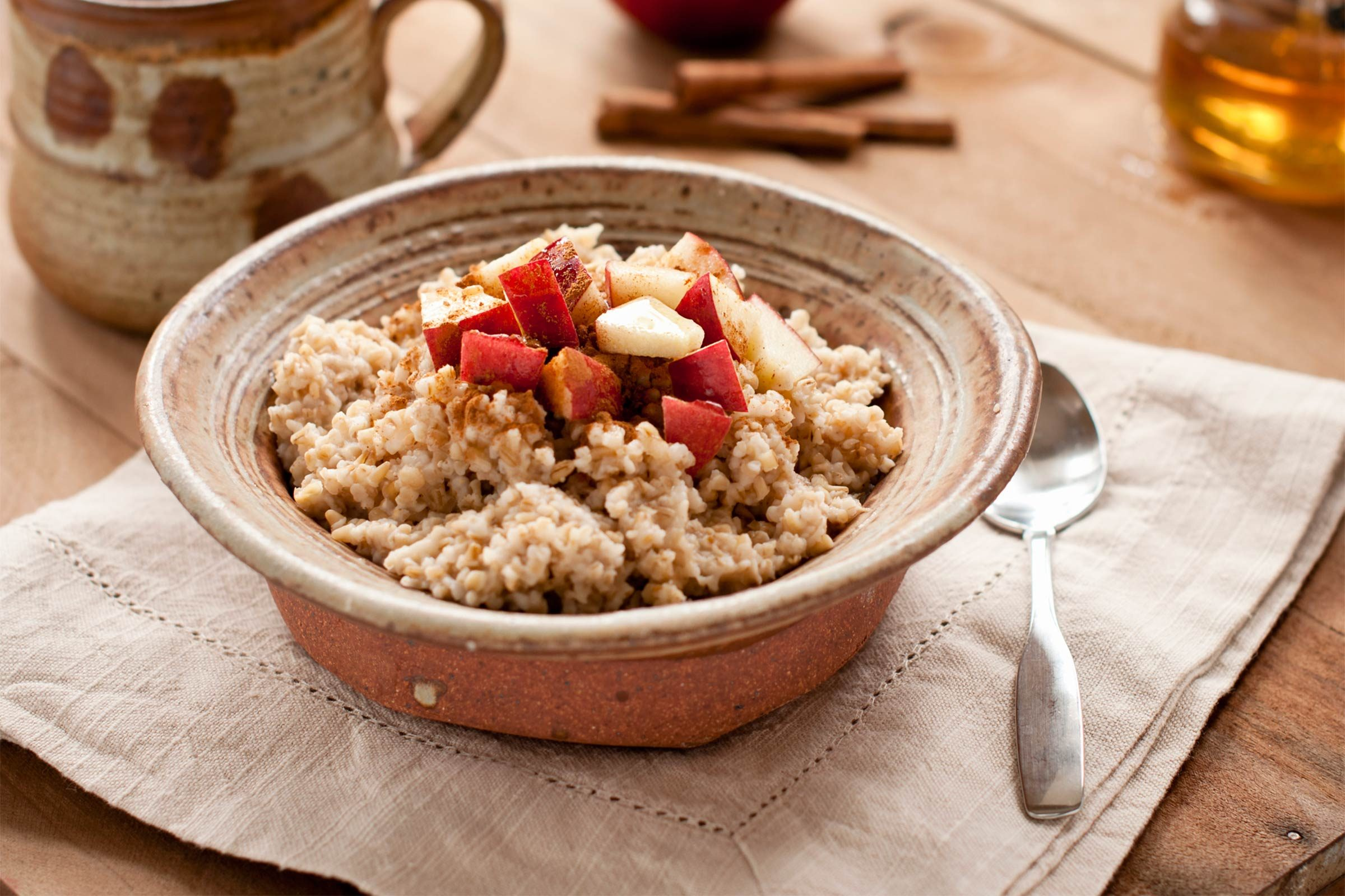 oatmeal with sliced apples in ceramic bowl