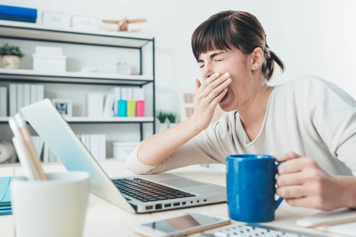 woman with a cup of coffee sitting at a desk in front of a laptop, yawning