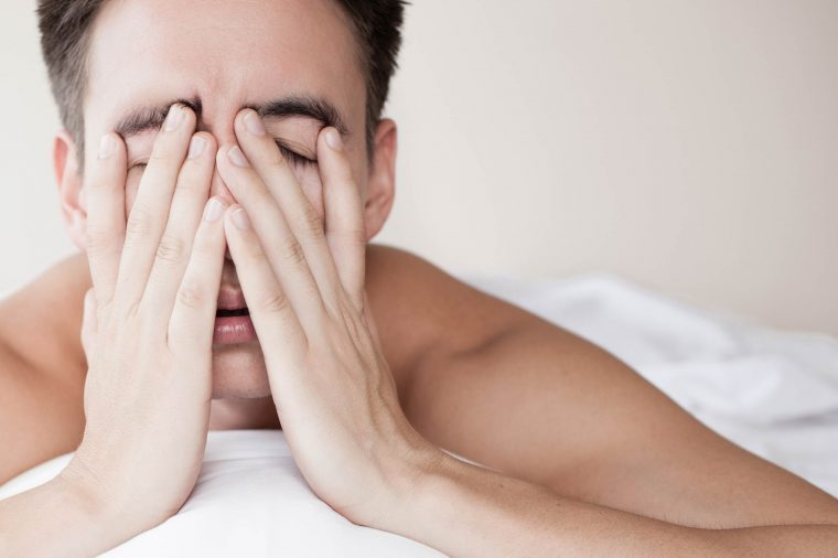 Sleepy man covering his face and lying on his bed.