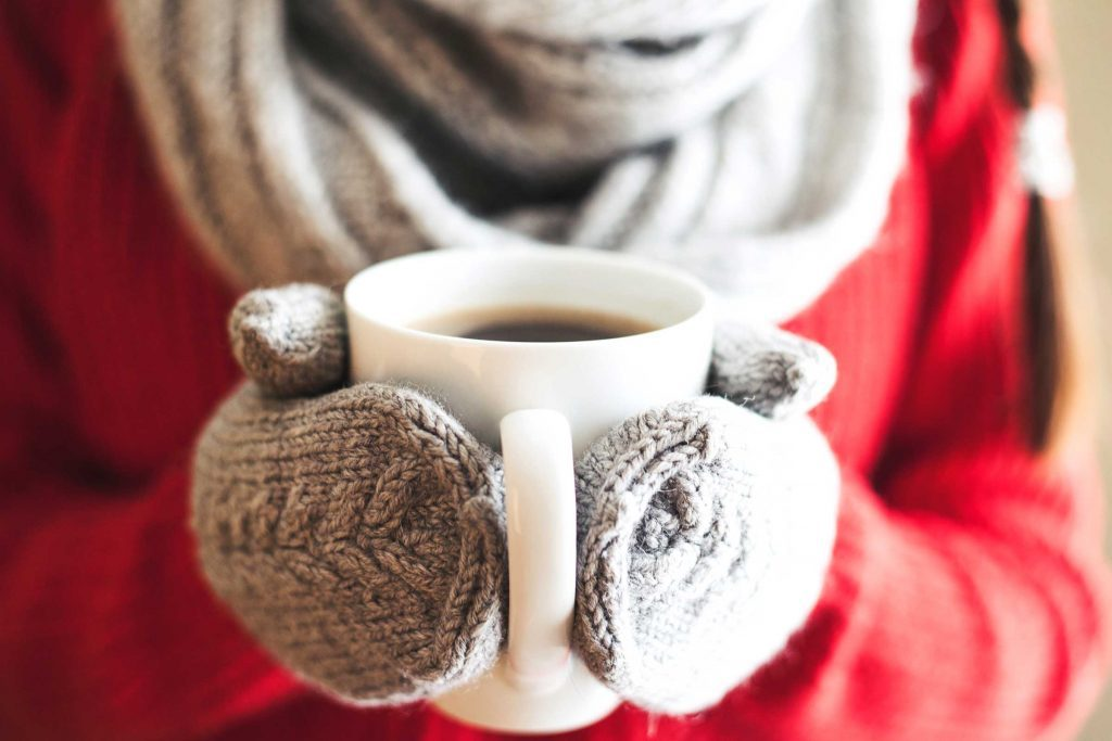 bundled up person with wool mittens holding a mug