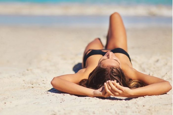 Woman in a black bathing suit laying on the sand at a beach.