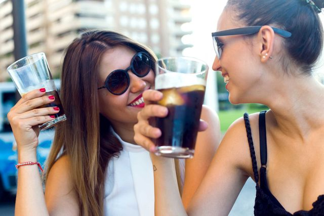 two woman holding glasses of cola