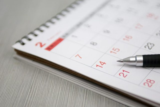Calendar resting on a gray surface with a pen on it.