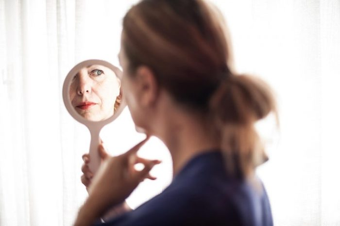 Woman looking in a hand mirror at her face.