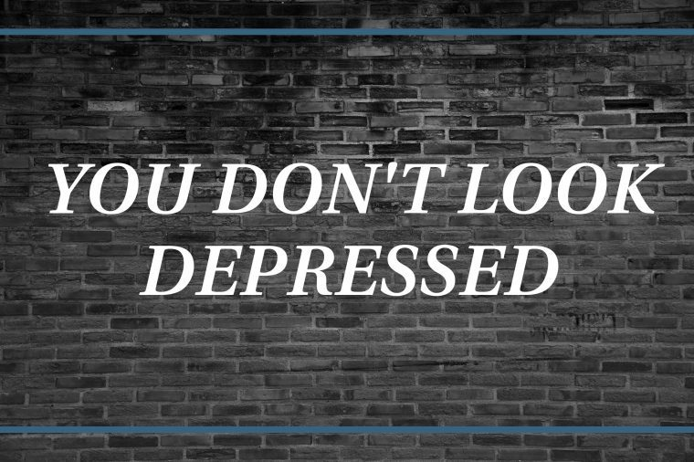 Brick wall background that says: You don't look depressed.