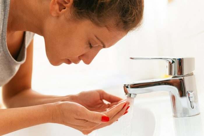 Woman washing her face with tap water in the sink.