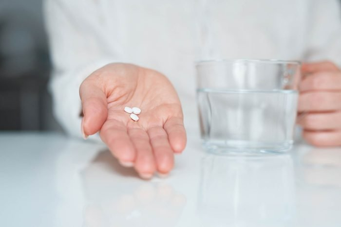 hand holding pills and a waterglass