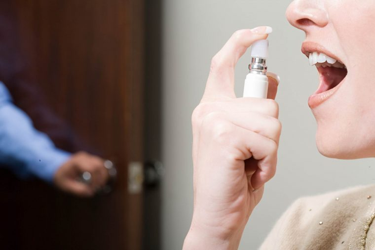 Woman spraying breathe freshener in mouth