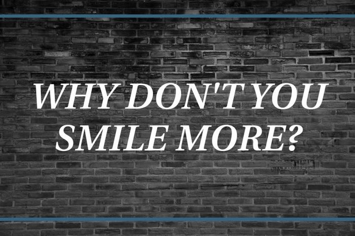 Brick wall background that says: Why don't you smile more?