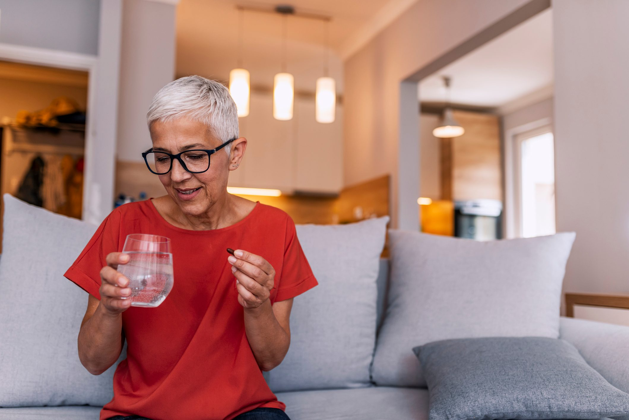 mature woman taking medication with glass of water at home