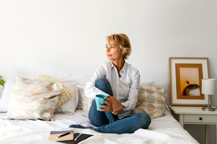 mature woman sitting on bed looking out window