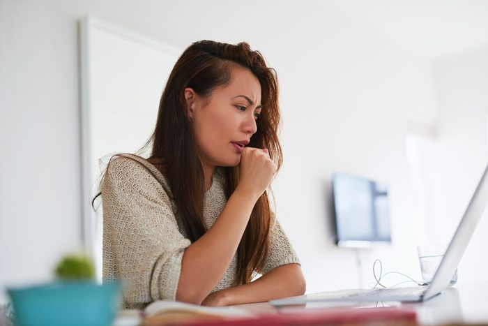 young woman coughing while working from home