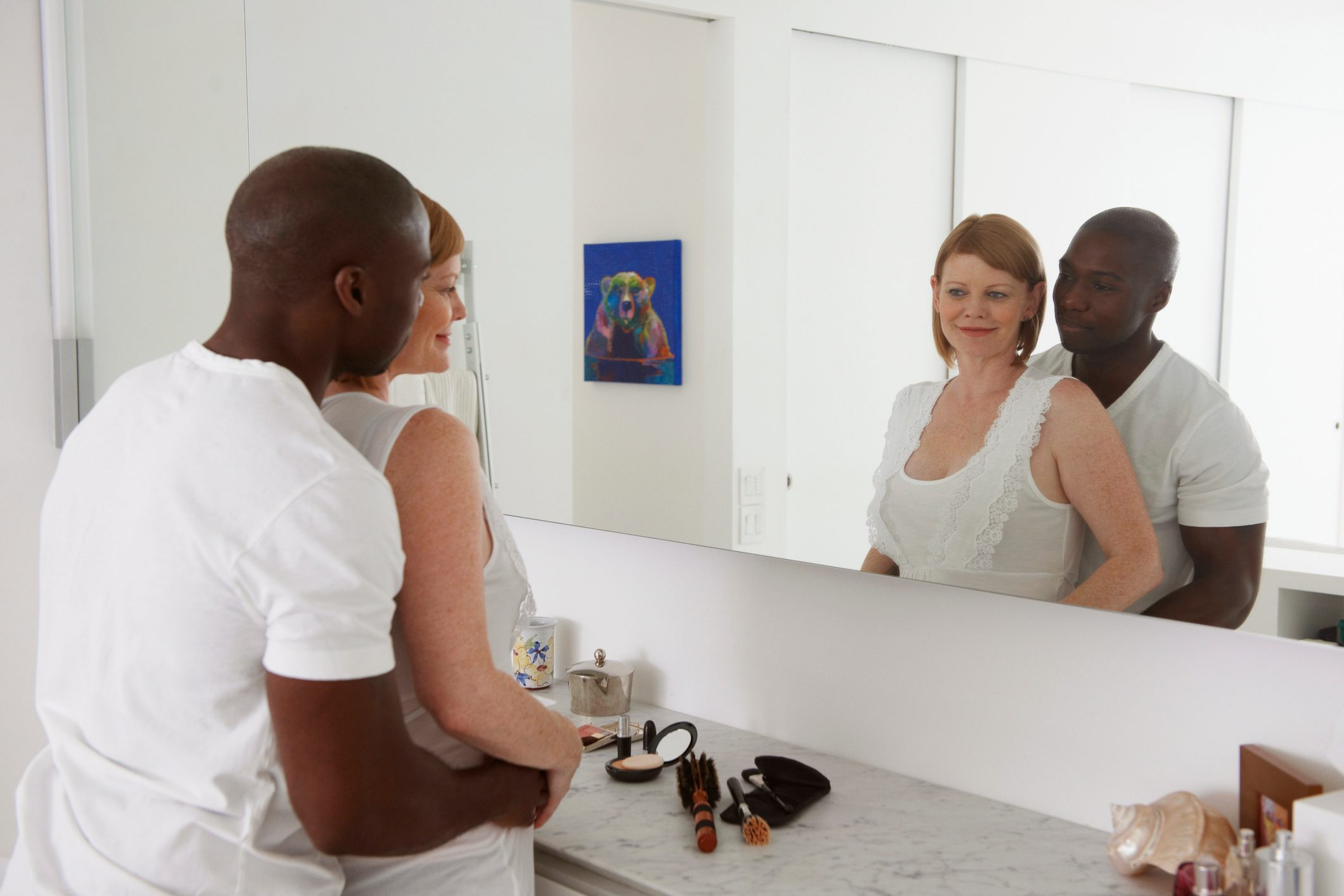 couple in the bathroom looking in mirror