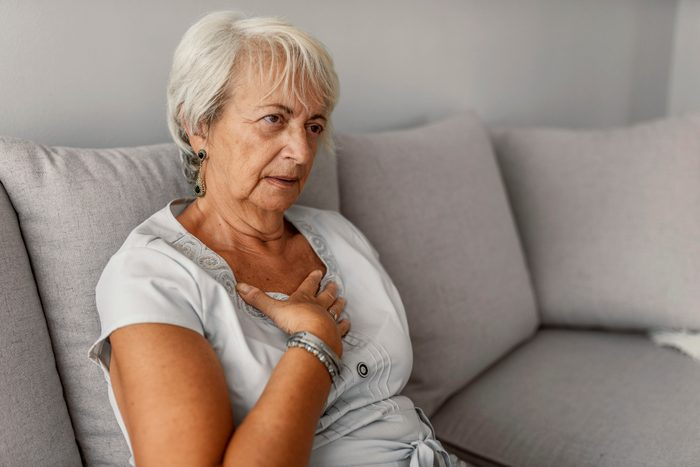 woman with shortness of breath while sitting on couch at home